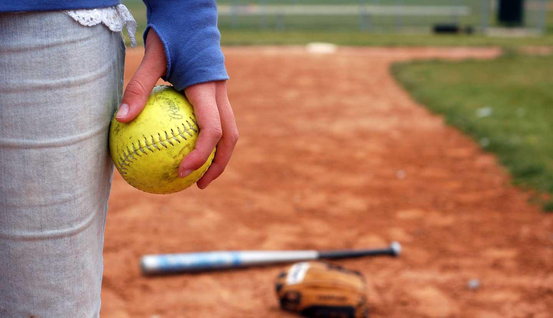 A girl holds a softball on the infield diamond.